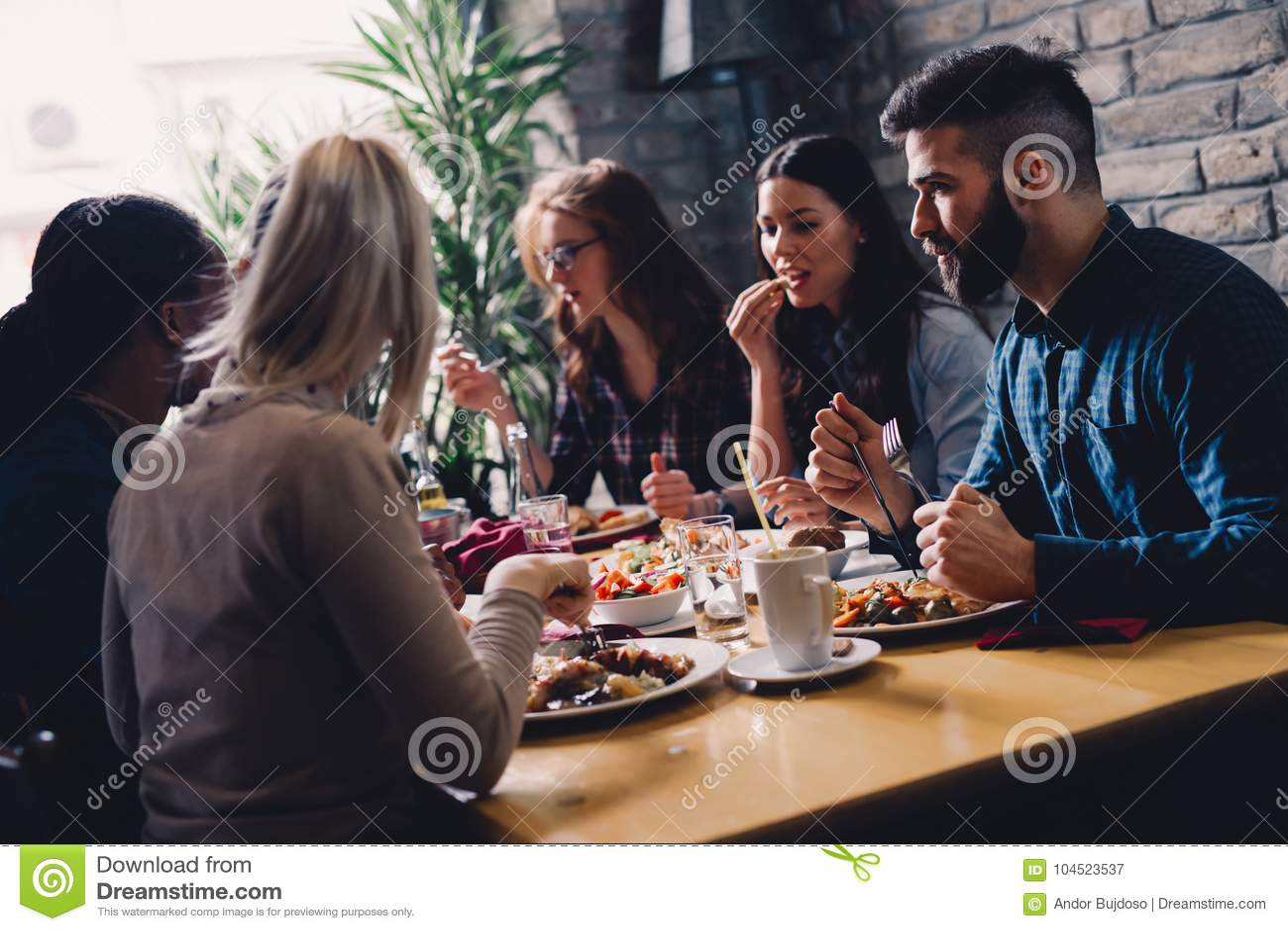 Grupo de executivos felizes que comem no restaurante