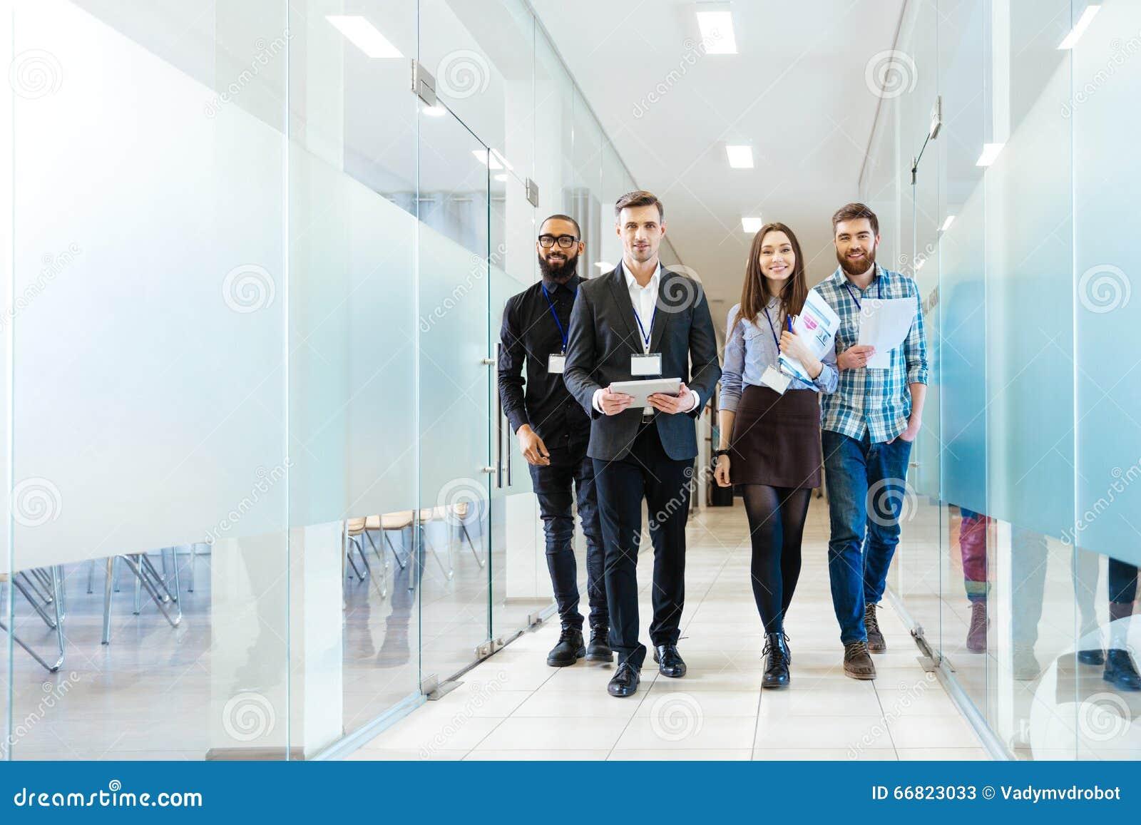Grupo de executivos novos felizes que andam no escritório junto