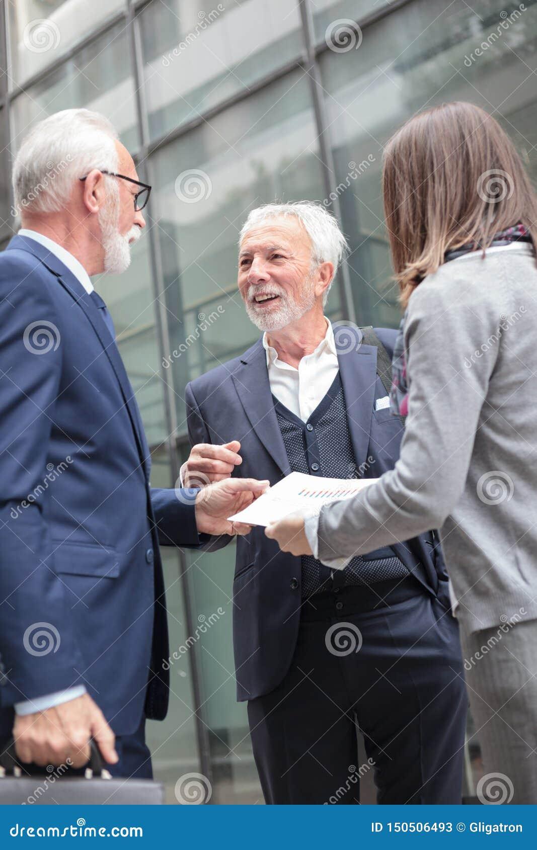 Grupo de executivos pequeno que encontram-se na rua fora de um prédio de escritórios, olhando relatórios de vendas