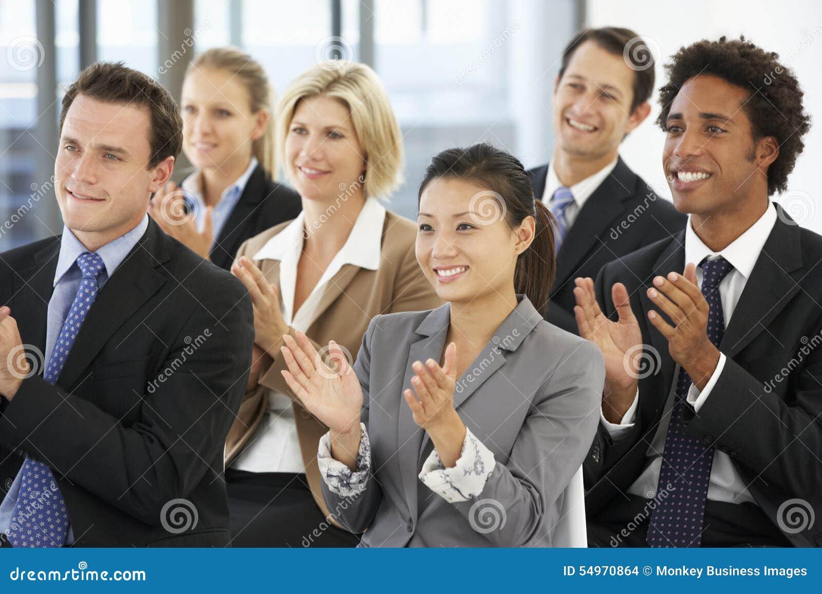Grupo de executivos que aplaudem o orador no fim de uma apresentação