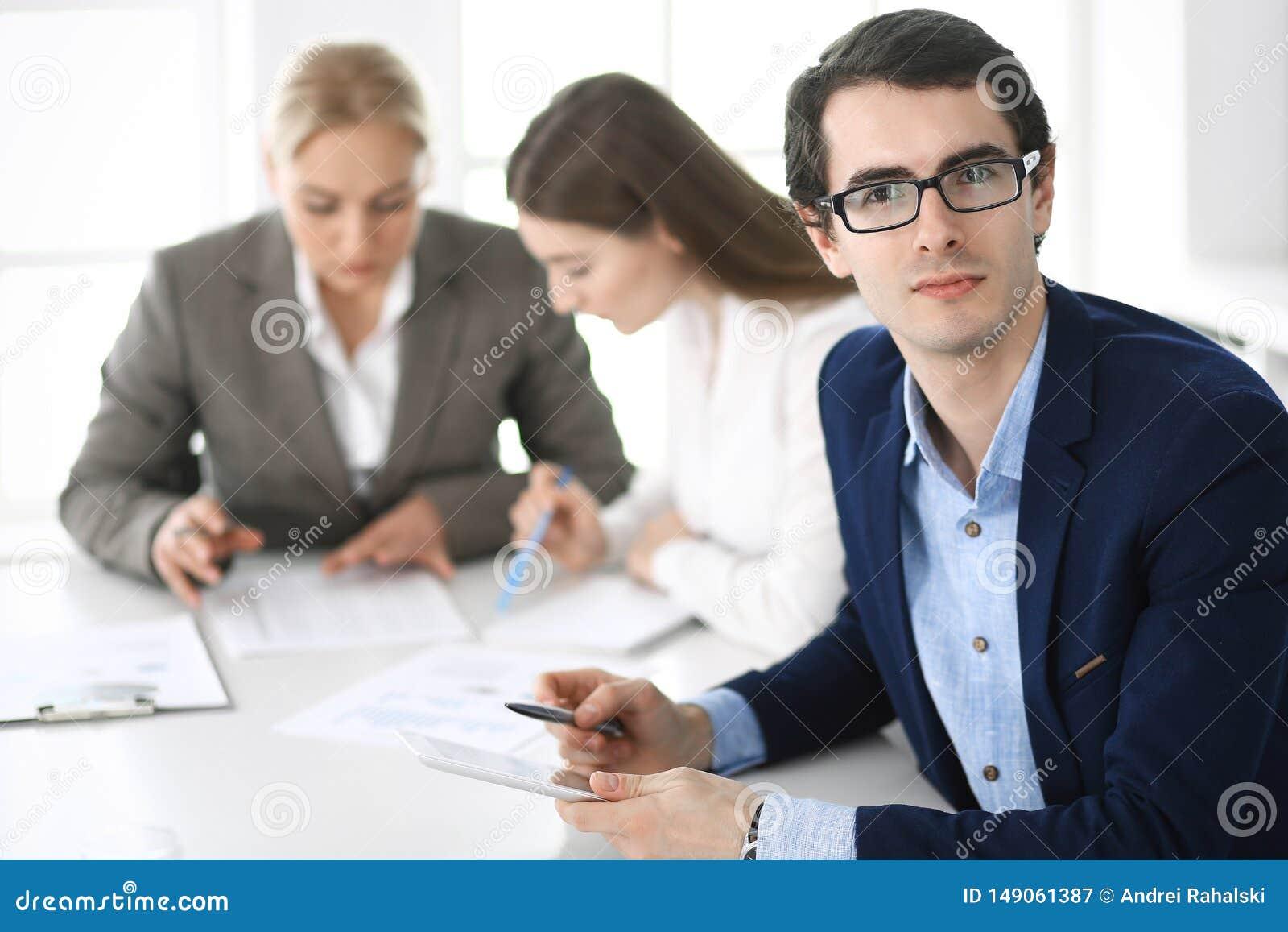 Grupo de executivos que discutem perguntas no encontro no escrit?rio moderno Headshot do homem de neg?cios na negocia??o