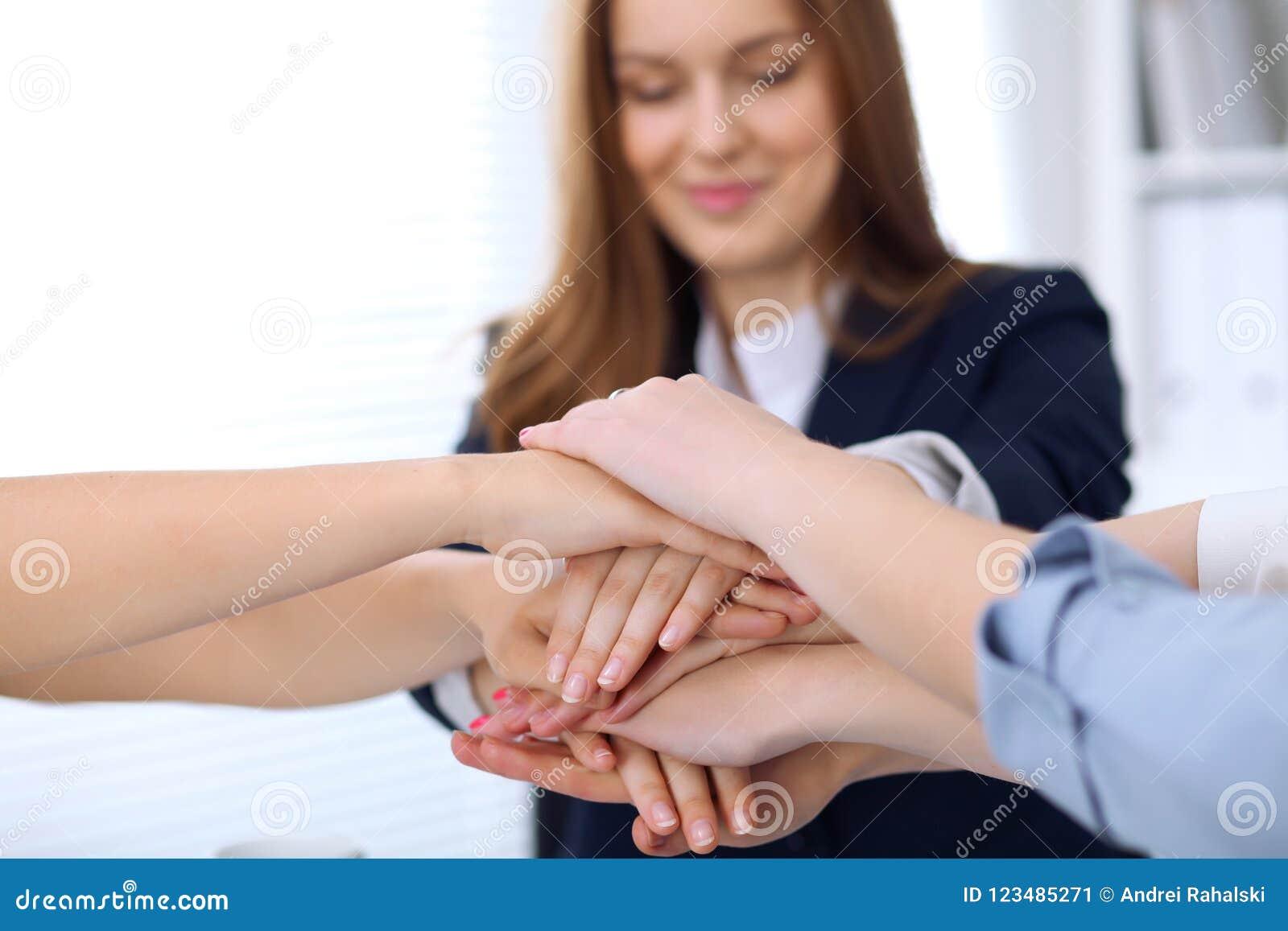 Grupo de executivos que juntam-se às mãos, close-up Conceito dos trabalhos de equipa, da cooperação e do sucesso de uma comunicaç
