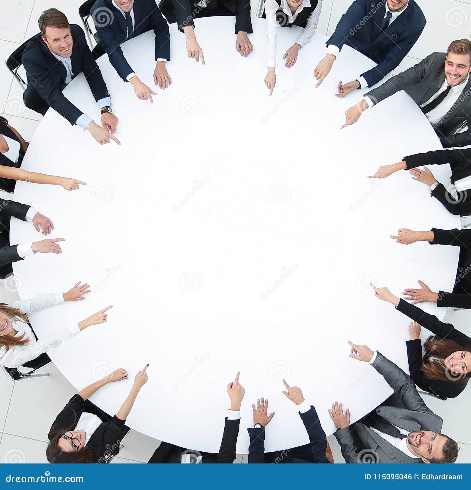 Grupo de executivos que sentam-se na mesa redonda O conceito do negócio