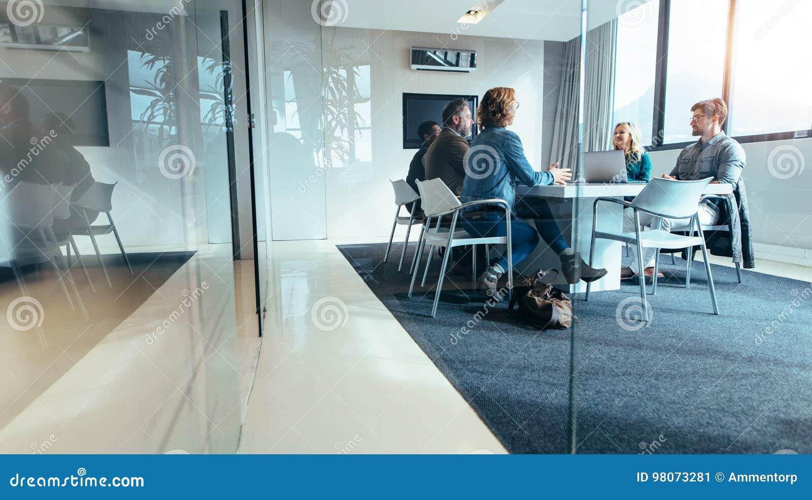 Grupo de executivos que têm a discussão na sala de conferências