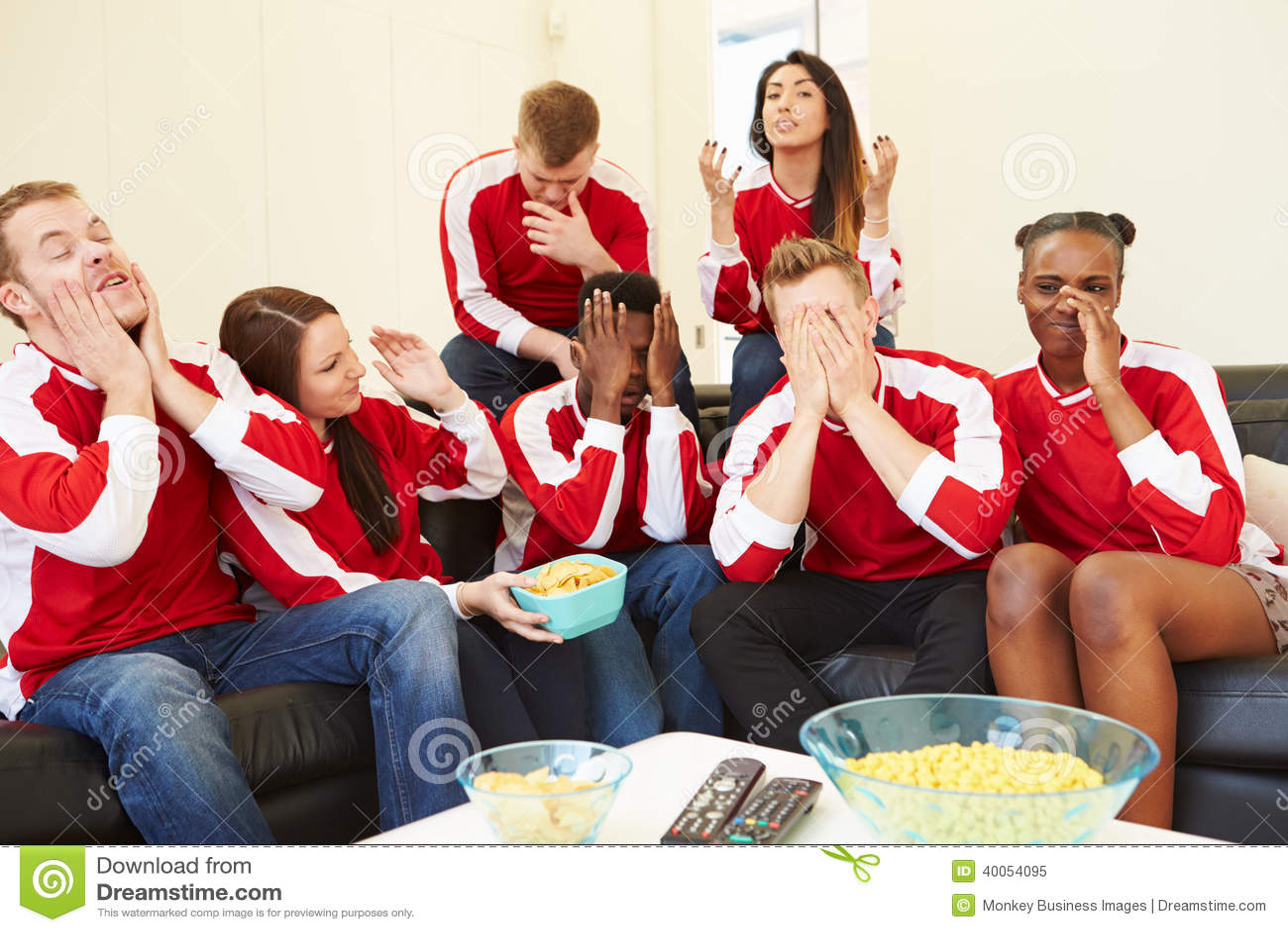 Grupo de fãs de esportes que olham o jogo na tevê em casa