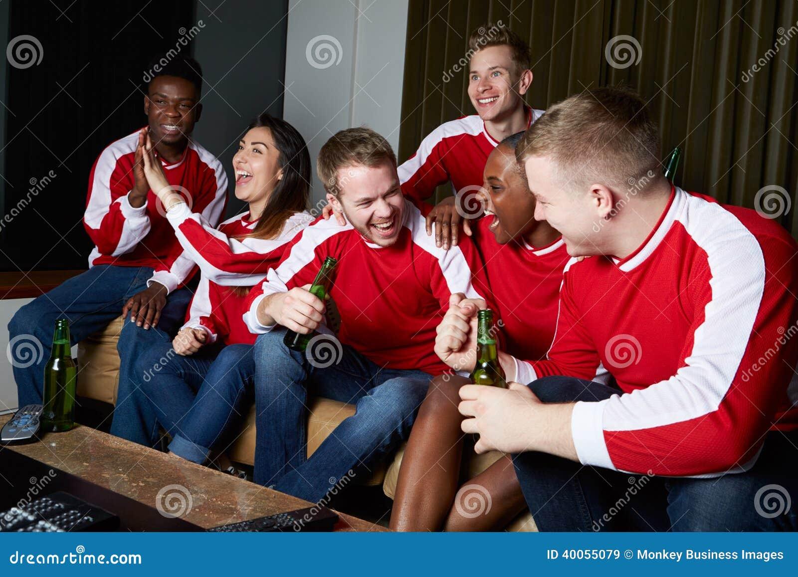 Grupo de fans de deportes que miran el juego en la TV en casa