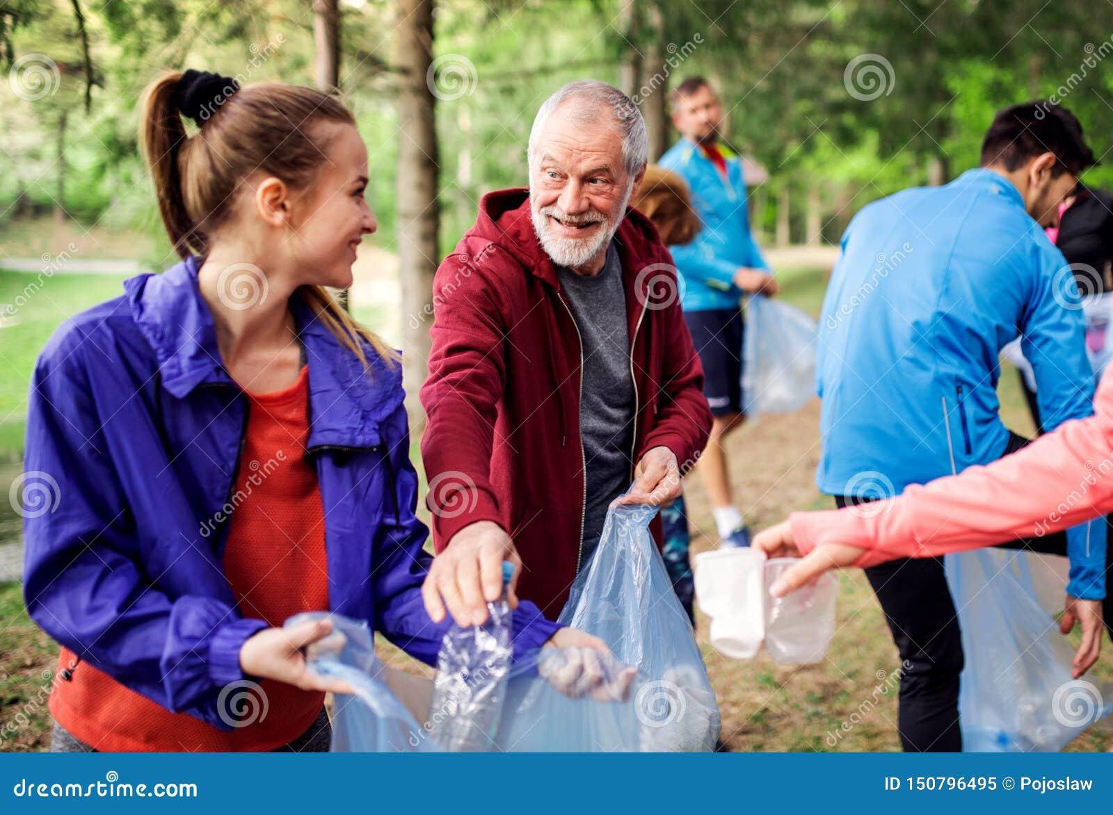 Grupo de gente apta que coge la litera en la naturaleza, un concepto plogging