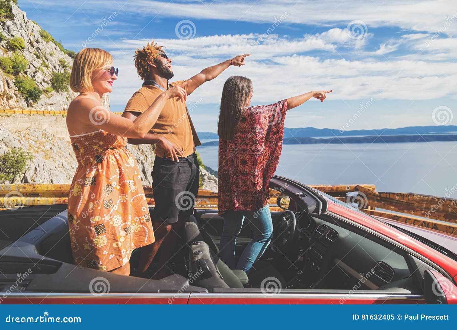 Grupo de gente feliz en coche convertible rojo