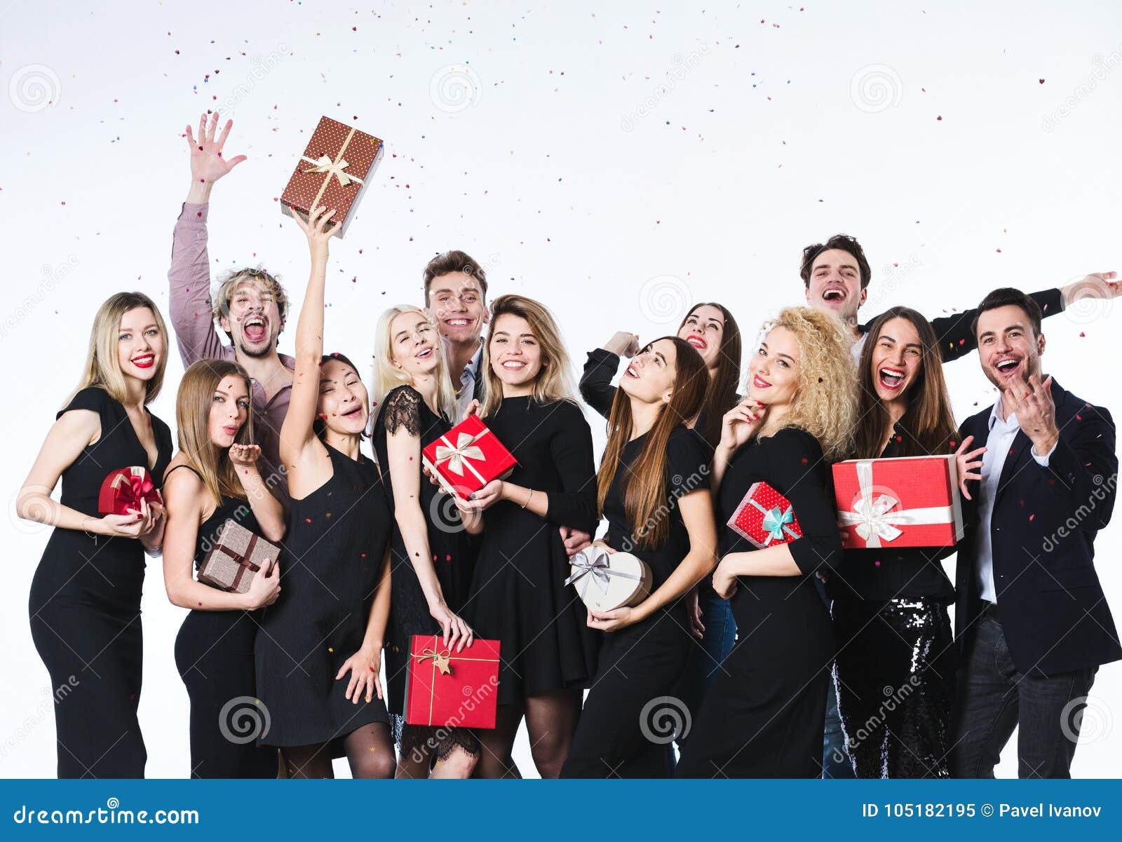 Grupo de gente hermosa joven en ropa elegante con las cajas de regalo en las manos que se divierten