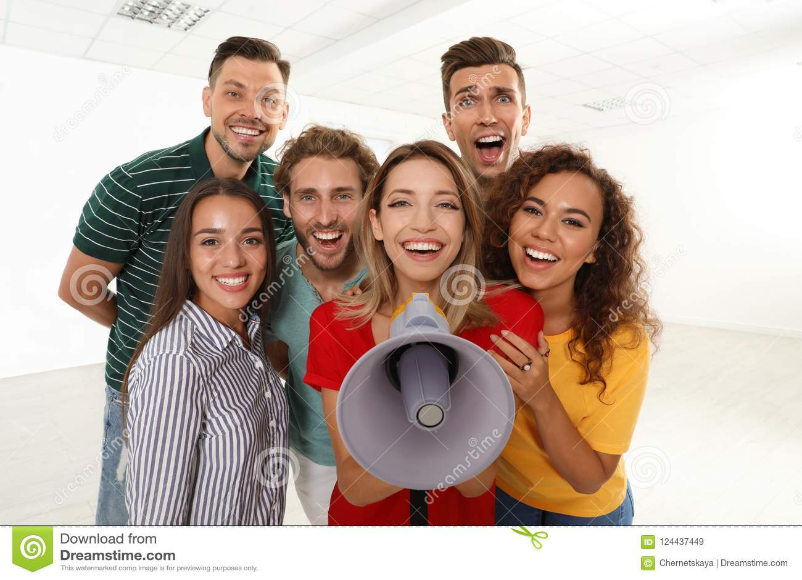 Grupo de gente joven feliz con el megáfono