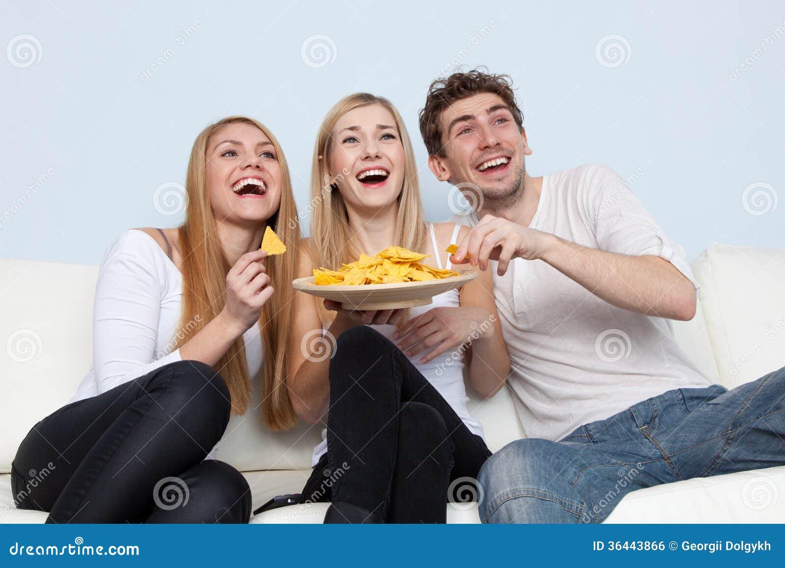 Grupo de gente joven que come la pizza en casa