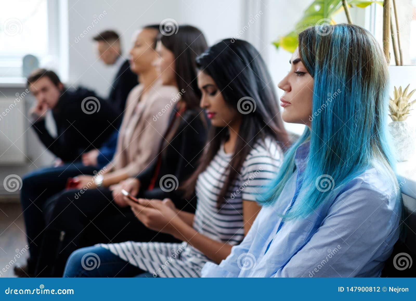 Grupo de gente joven que espera una entrevista del bastidor o de trabajo