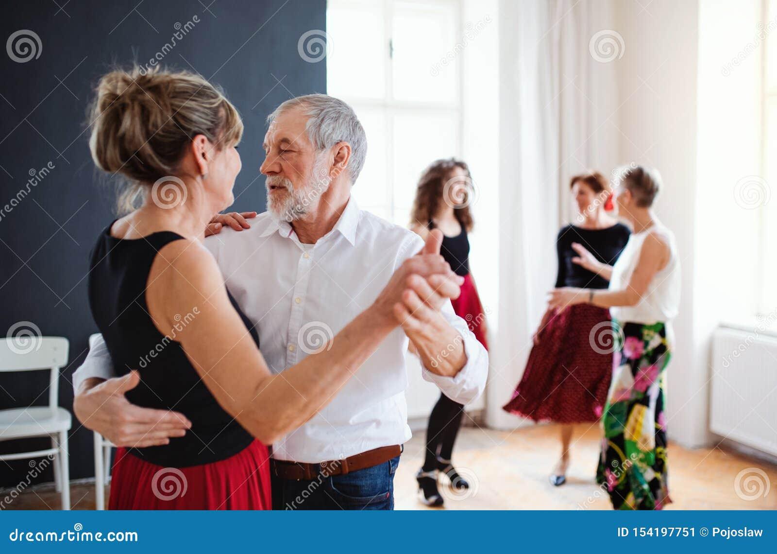 Grupo de gente mayor en clase de baile con el profesor de la danza