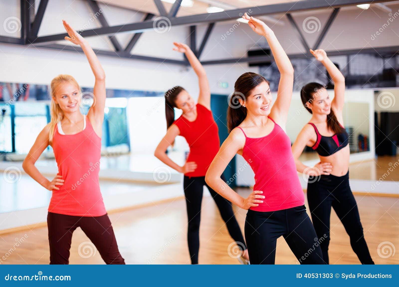Grupo de gente sonriente que estira en el gimnasio foto de for Gimnasio gimnasio
