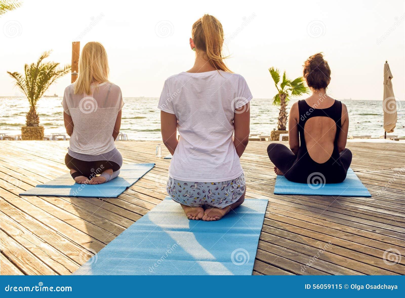 Grupo de hembras jovenes que practican yoga en la playa durante la salida del sol