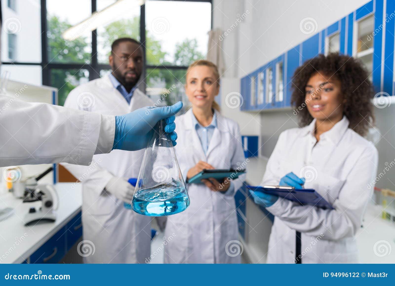 Grupo de Holding Flask With del científico de estudiantes que toman las notas que hacen la investigación en el laboratorio, raza