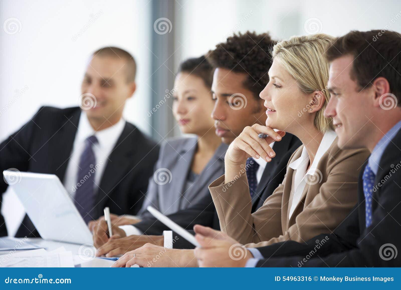 Grupo de hombres de negocios que escuchan el colega que dirige la reunión de la oficina
