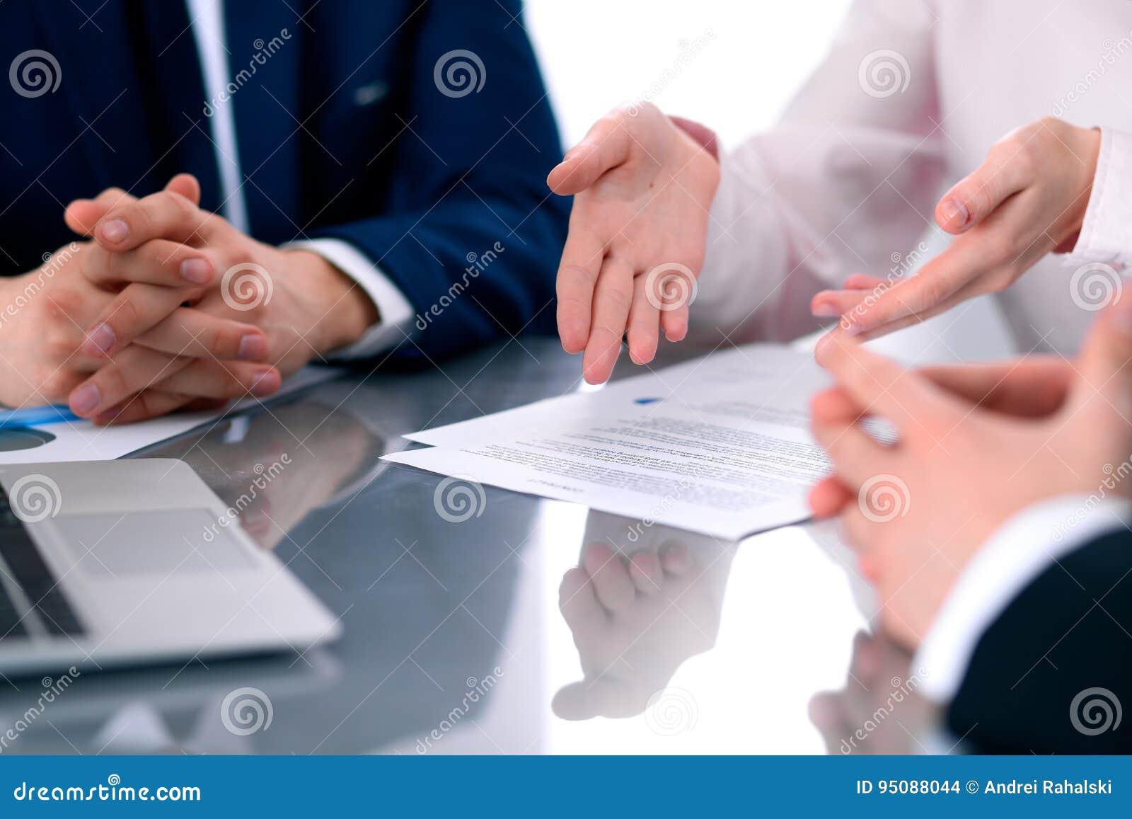 Grupo de hombres de negocios y de abogados que discuten los papeles del contrato