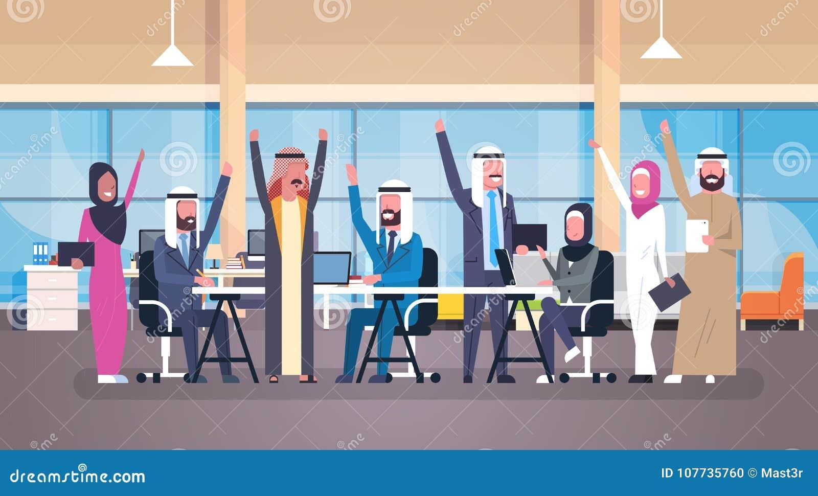 Grupo de hombres de negocios árabes alegres de las manos aumentadas control feliz que se sientan junto en el equipo musulmán de l