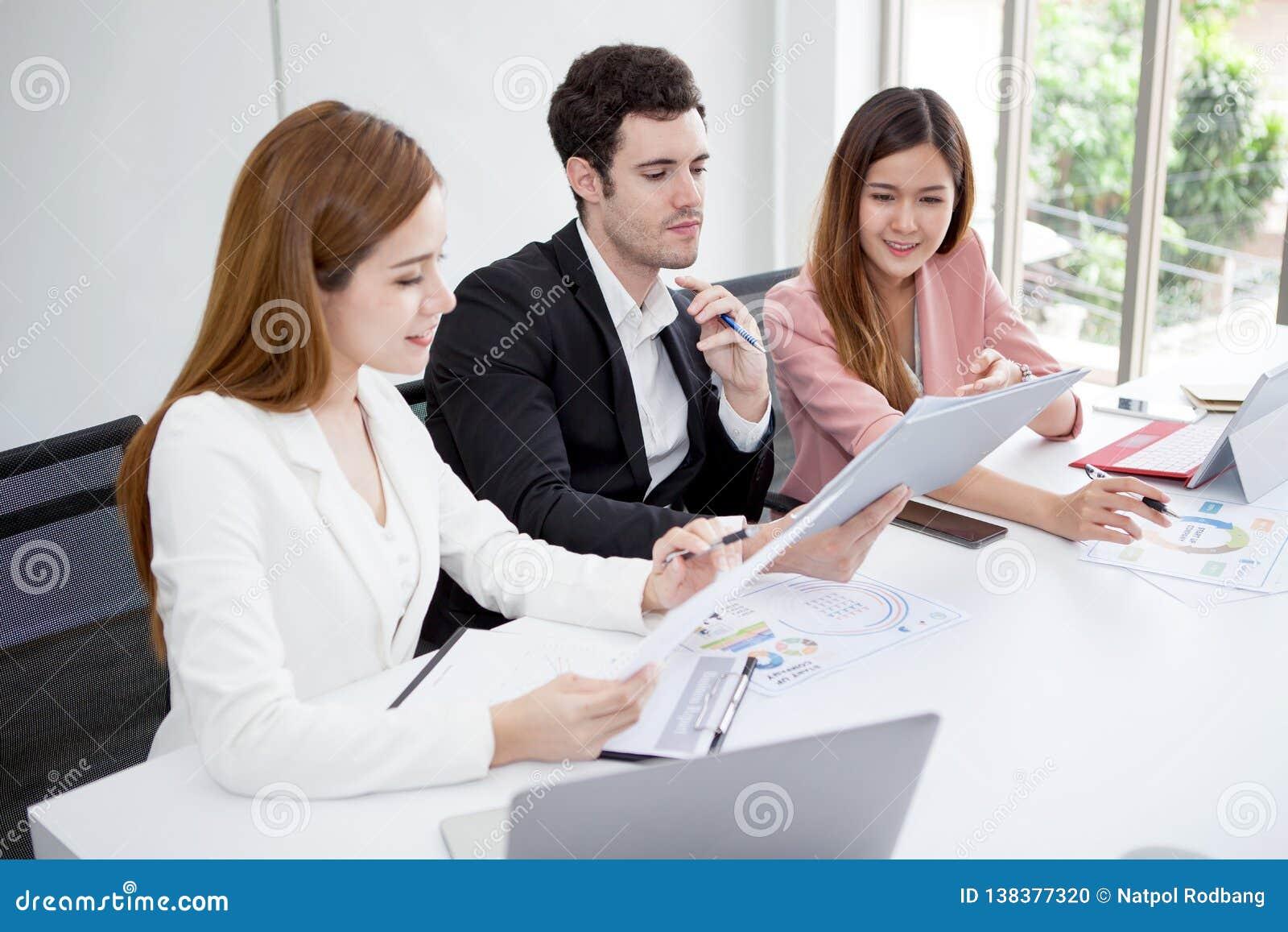Grupo de hombres de negocios felices de los hombres y mujer que trabajan así como fichero de documento de papel en sala de reunió