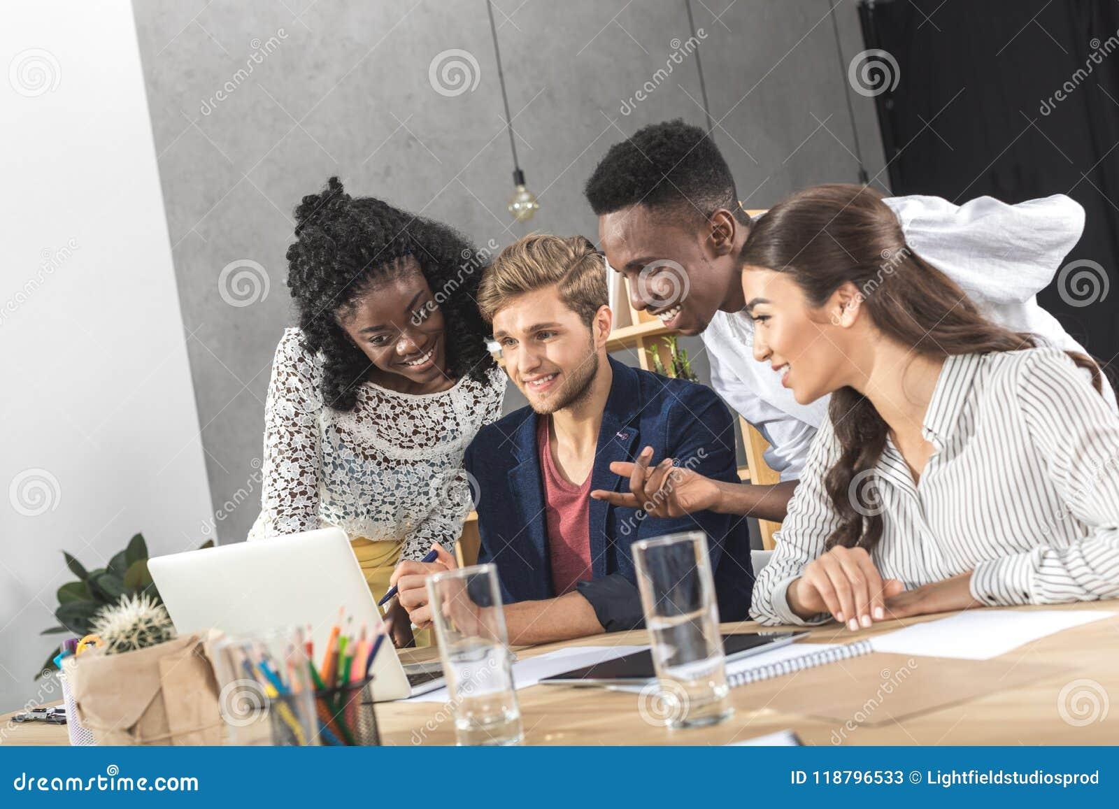 Grupo de hombres de negocios multicultural que usan el ordenador portátil junto en el lugar de trabajo