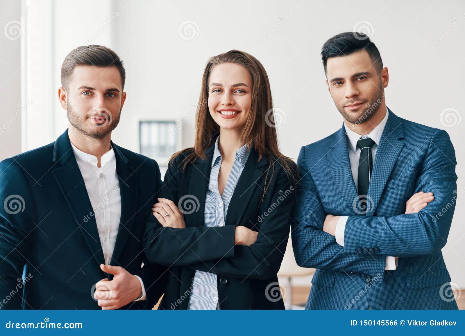 Grupo de hombres de negocios sonrientes acertados con con los brazos cruzados en oficina