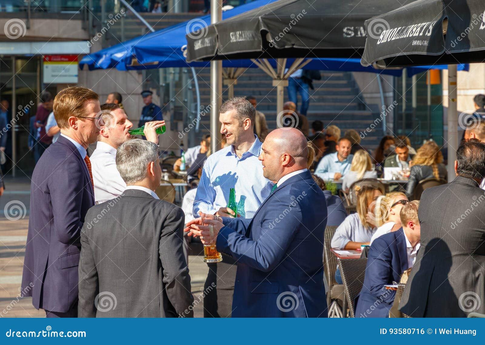 Grupo de homens de negócios que bebem em uma barra exterior em Canary Wharf