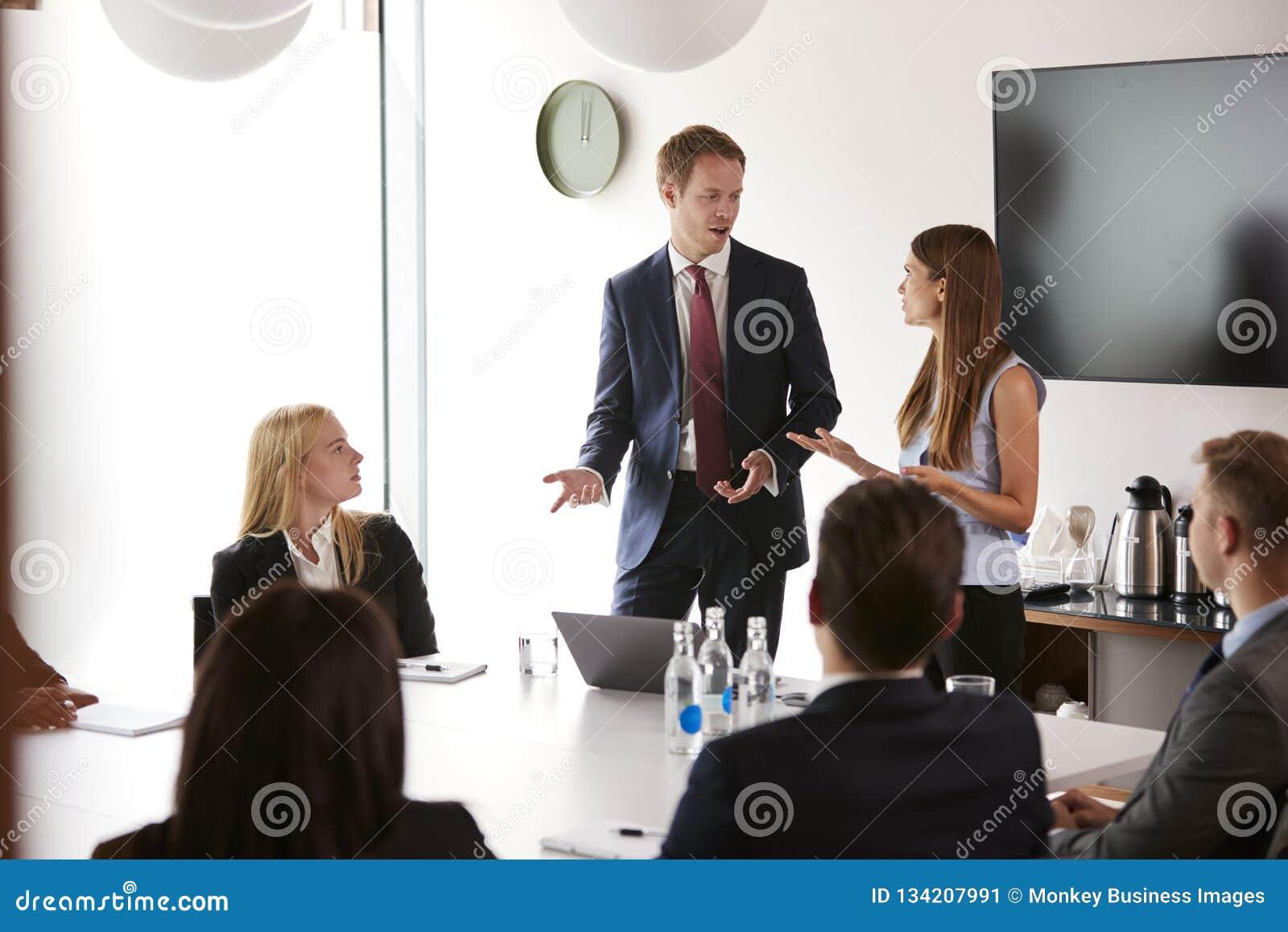 Grupo de homens de negócios novos e de mulheres de negócios que encontram-se em torno da tabela no dia graduado da avaliação do r