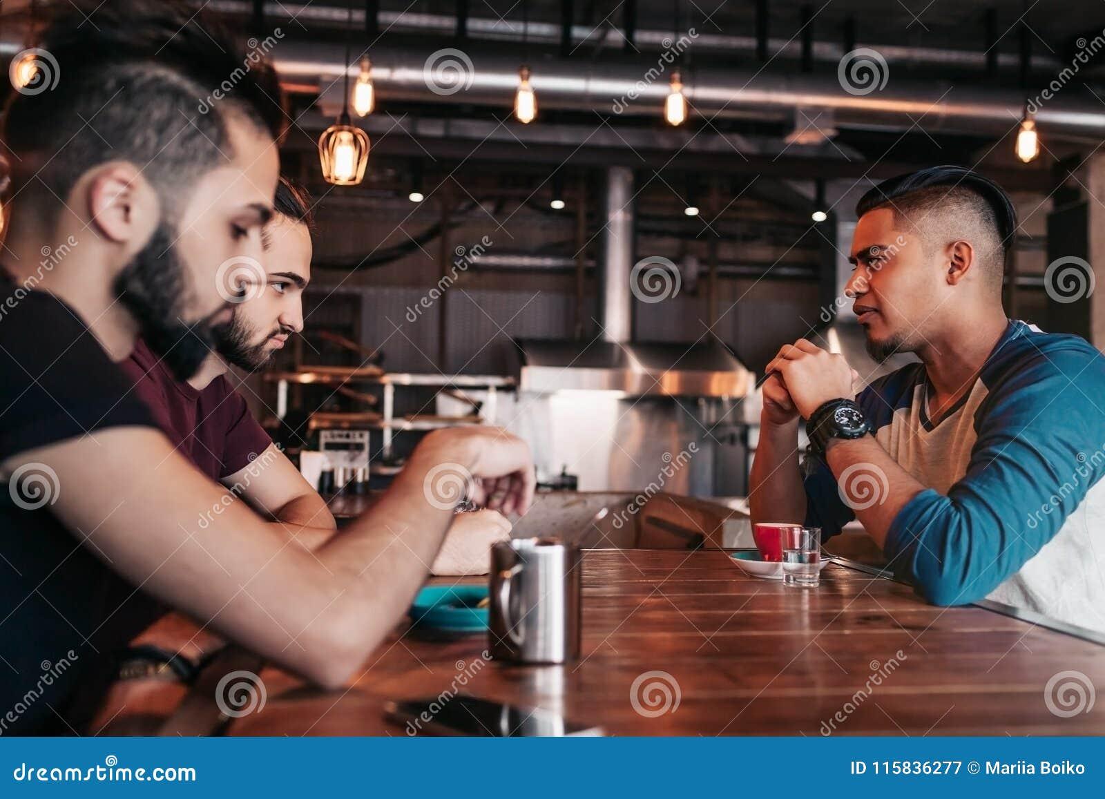 Grupo de homens novos de raça misturada que falam e que riem no restaurante Amigos multirraciais que têm o divertimento no café L