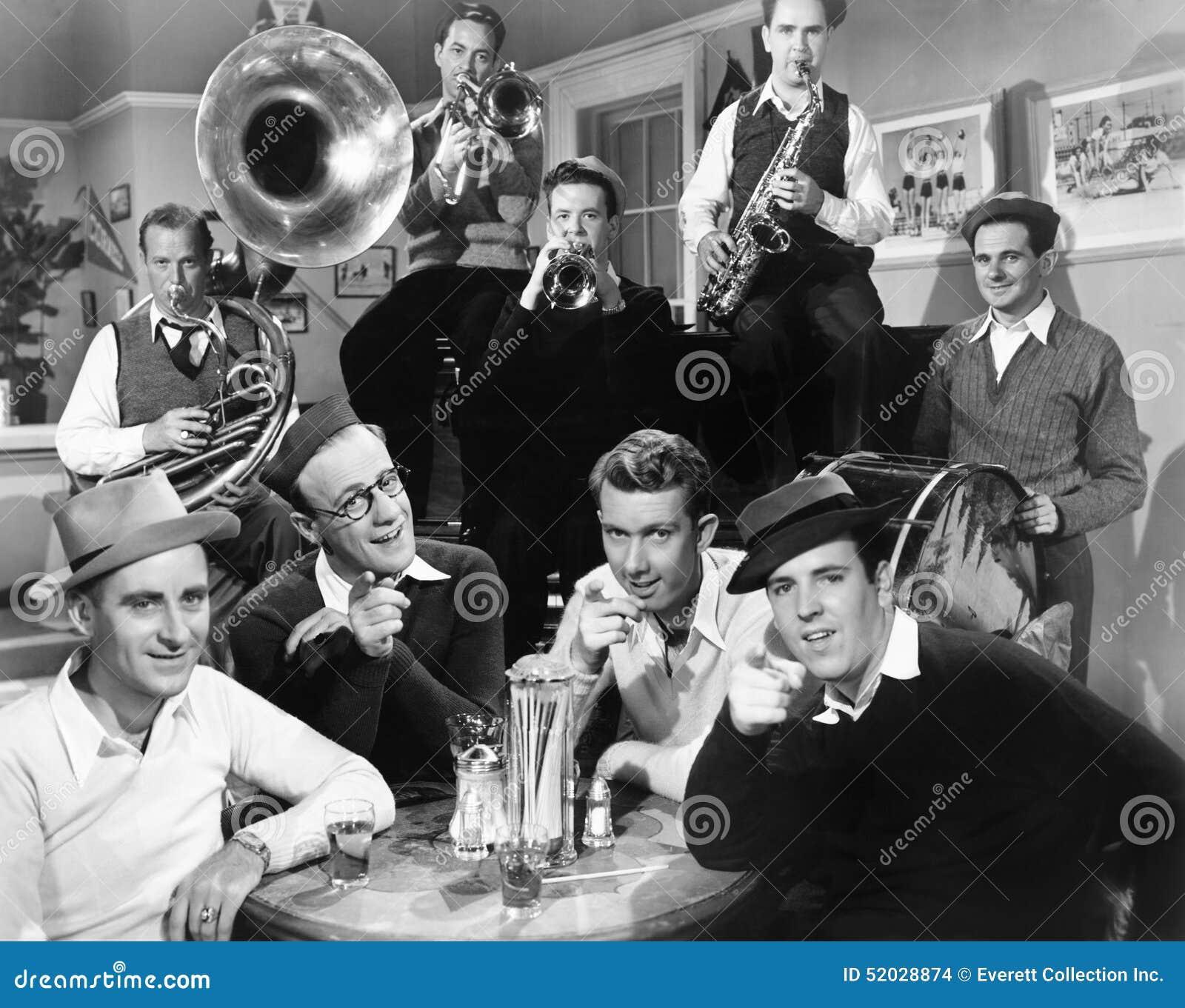 Grupo de homens que sentam se em um jantar com os músicos atrás  #666666 1300x1123