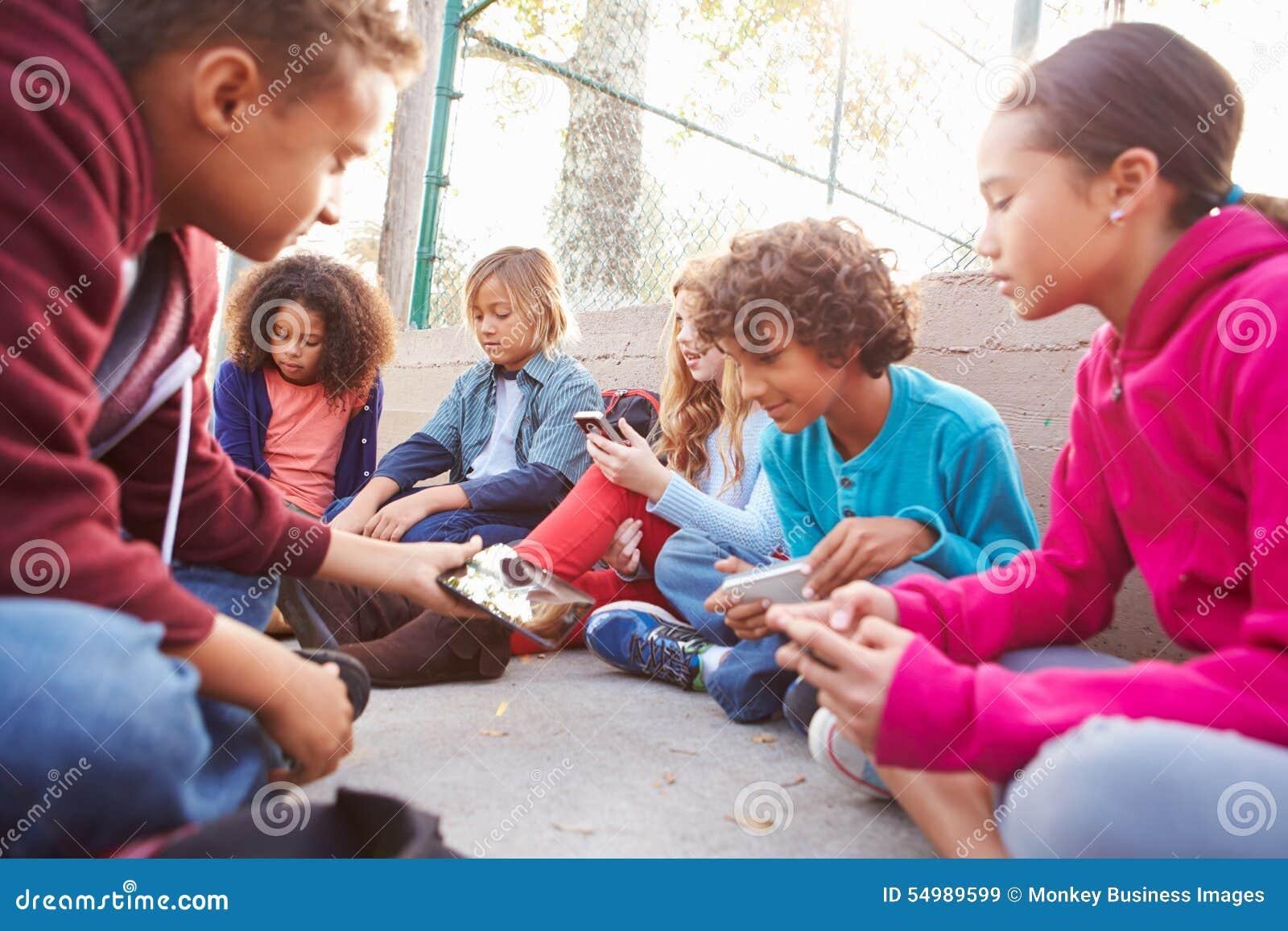 Grupo de jovens crianças que penduram para fora no campo de jogos