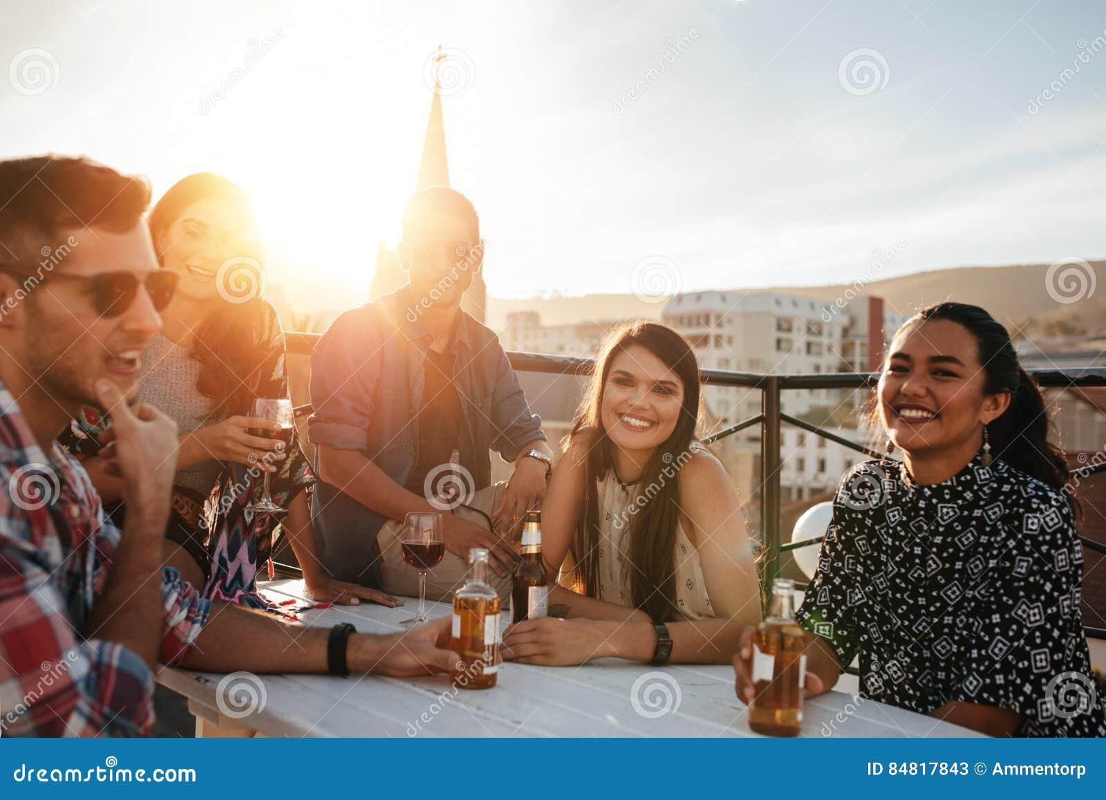 Grupo de jovens felizes que têm o partido