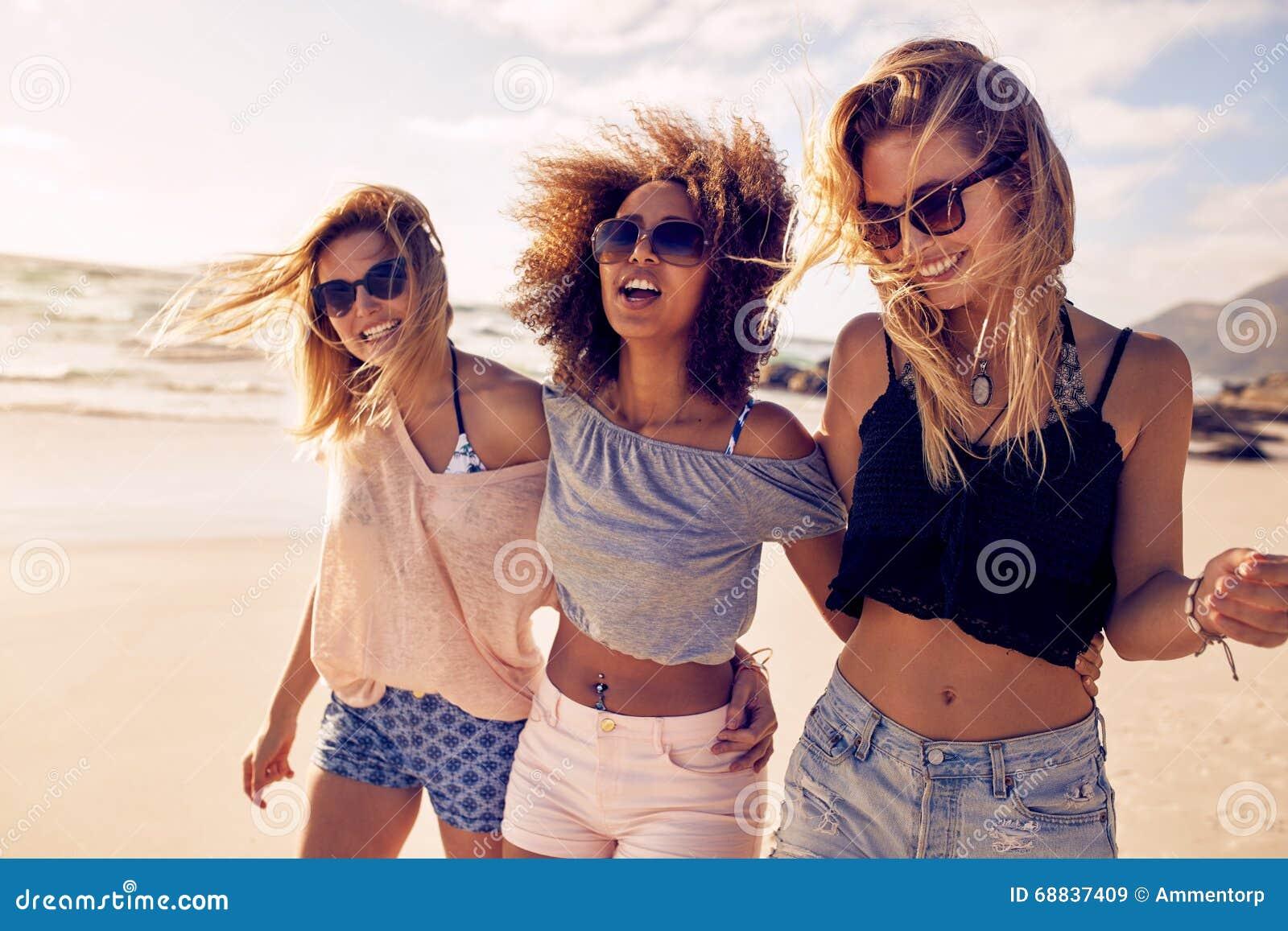 Grupo de jovens mulheres bonitas que dão uma volta em uma praia