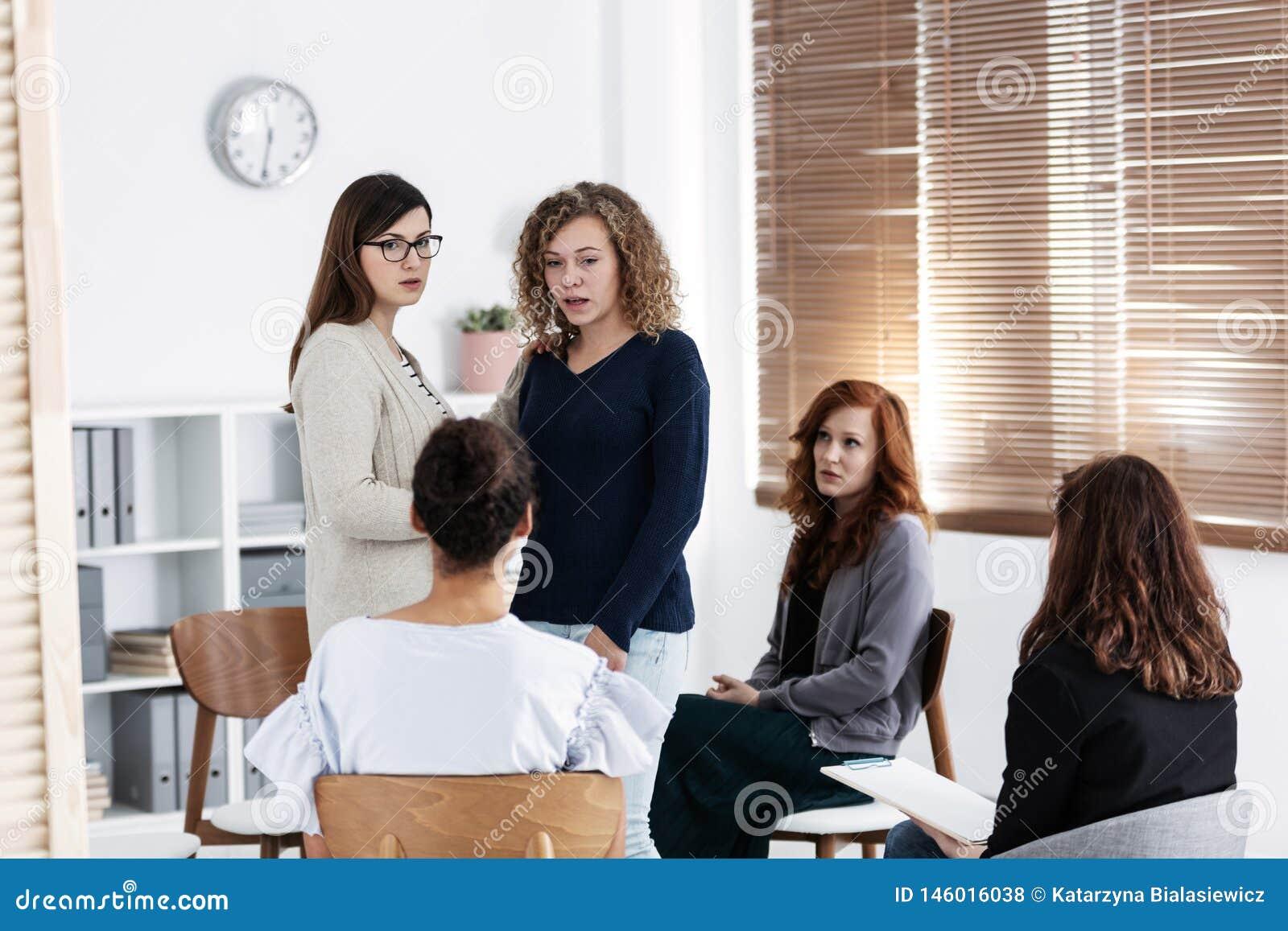 Grupo de jovens mulheres que falam o assento em um c?rculo Conceito psicol?gico do apoio