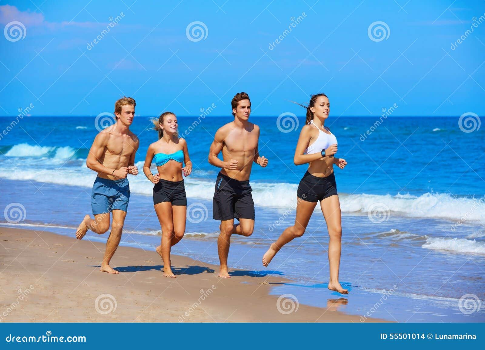 Grupo de jovens que correm na praia
