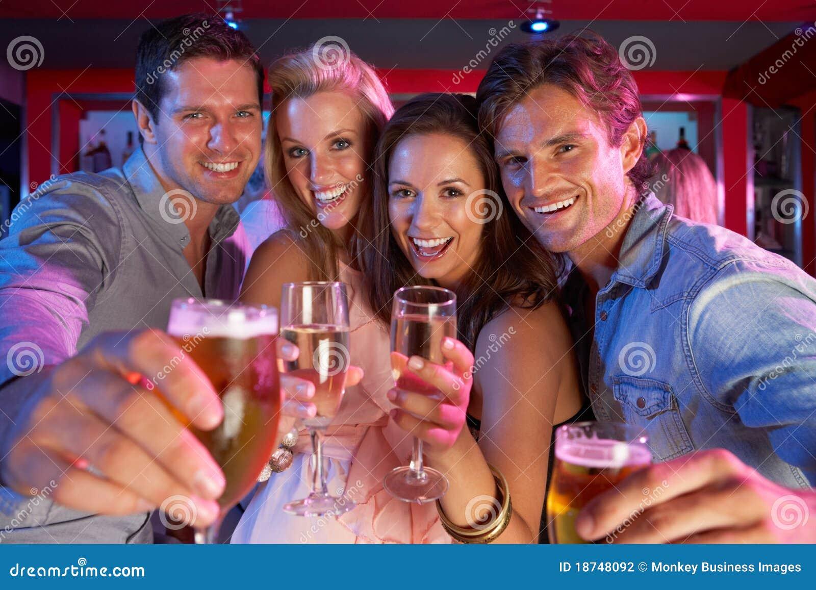 Grupo de jovens que têm o divertimento na barra ocupada
