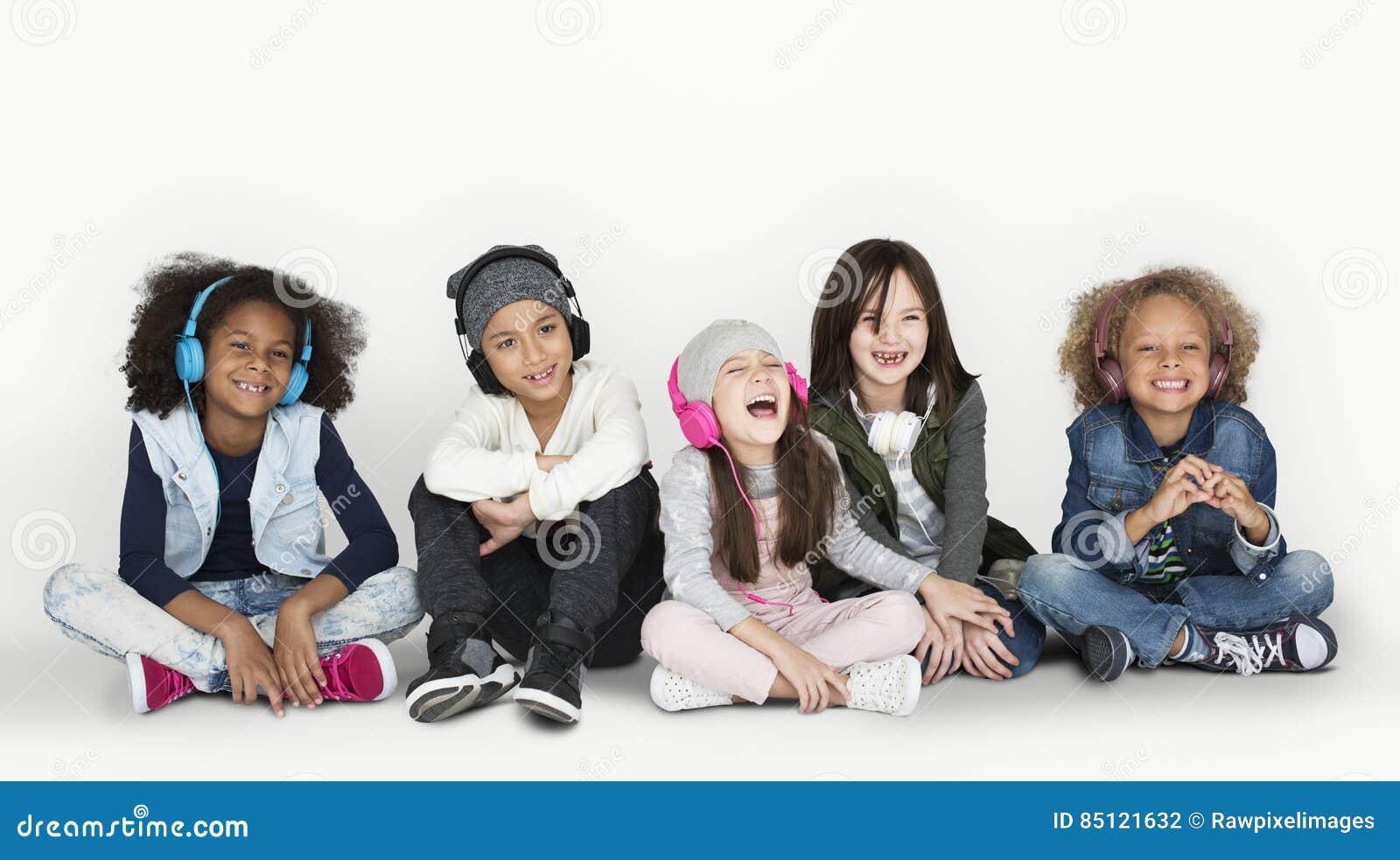 Grupo de los auriculares que llevan sonrientes y del invierno C del estudio de los niños