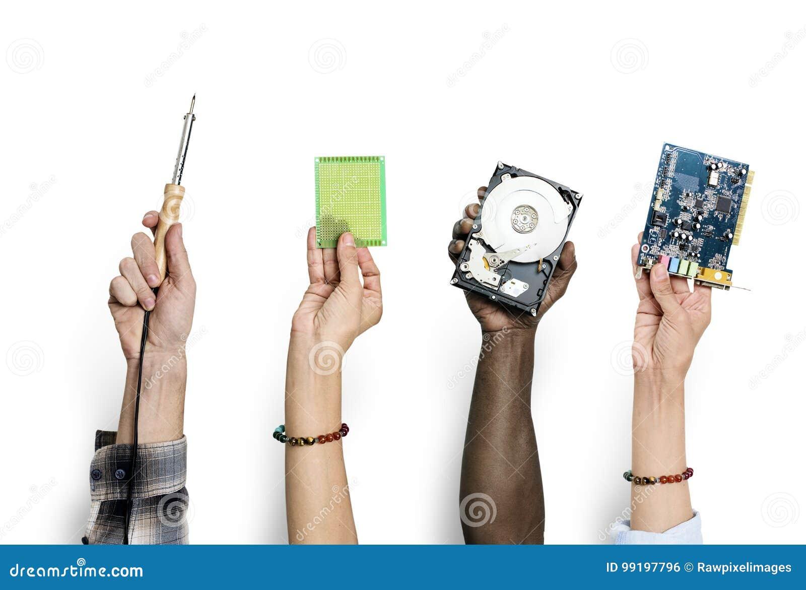 Grupo de mãos que mantêm as peças da eletrônica do computador isoladas no branco