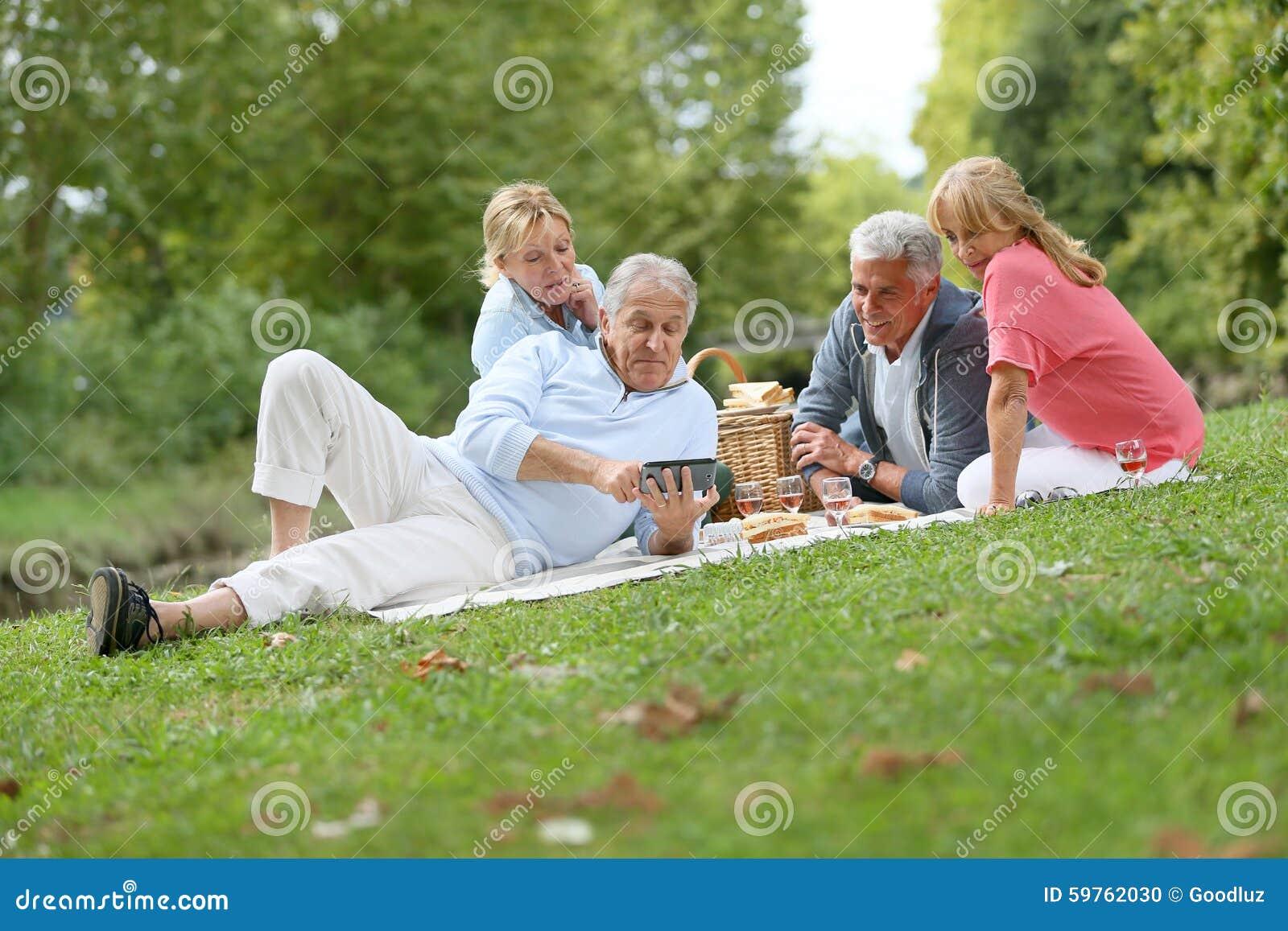 Grupo de mayores que tienen comida campestre al aire libre