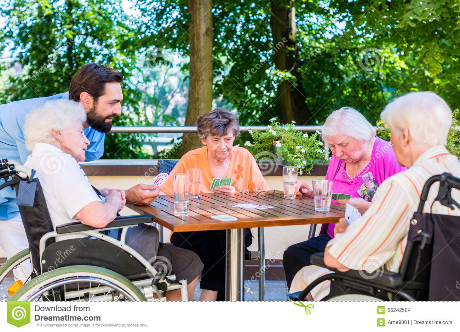 Grupo de mayores y de naipes de la enfermera en hogar de resto