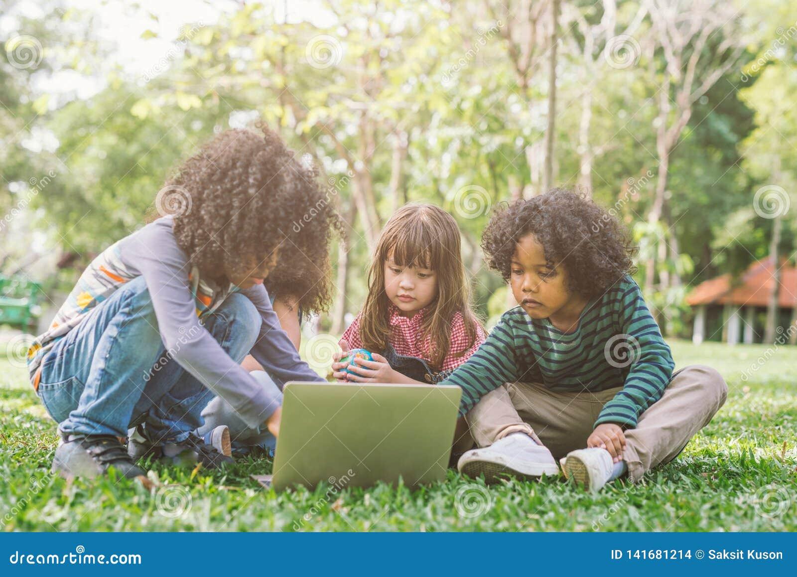 Grupo de miúdos com portátil crianças felizes na natureza com grupo de amigo