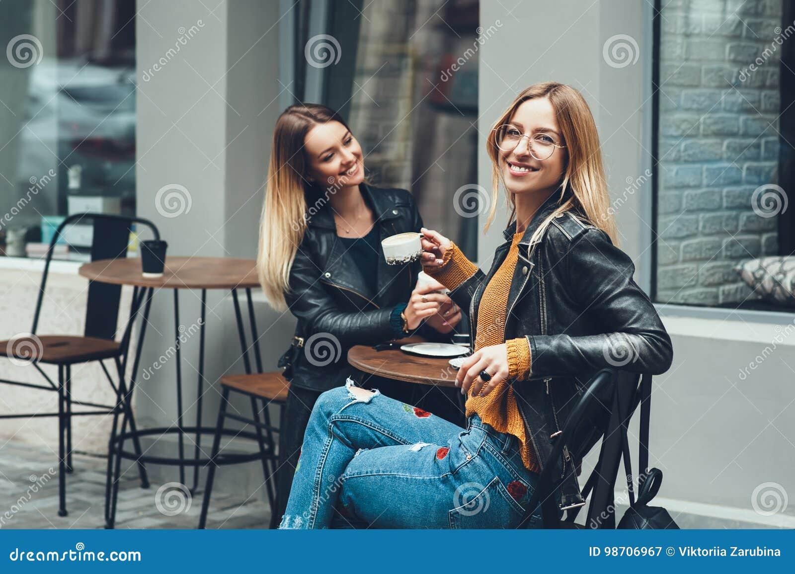 Grupo de muchachas europeas que comen un café junto Dos mujeres en el café que hablan, riendo, cotilleando y disfrutando de su ti