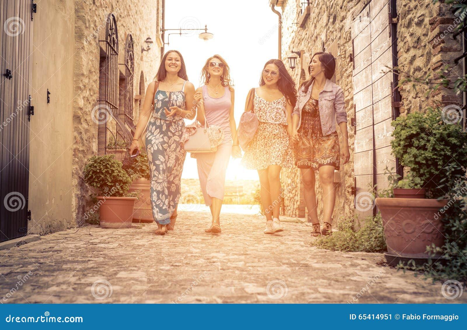 Grupo de muchachas que caminan en un centro histórico en Italia
