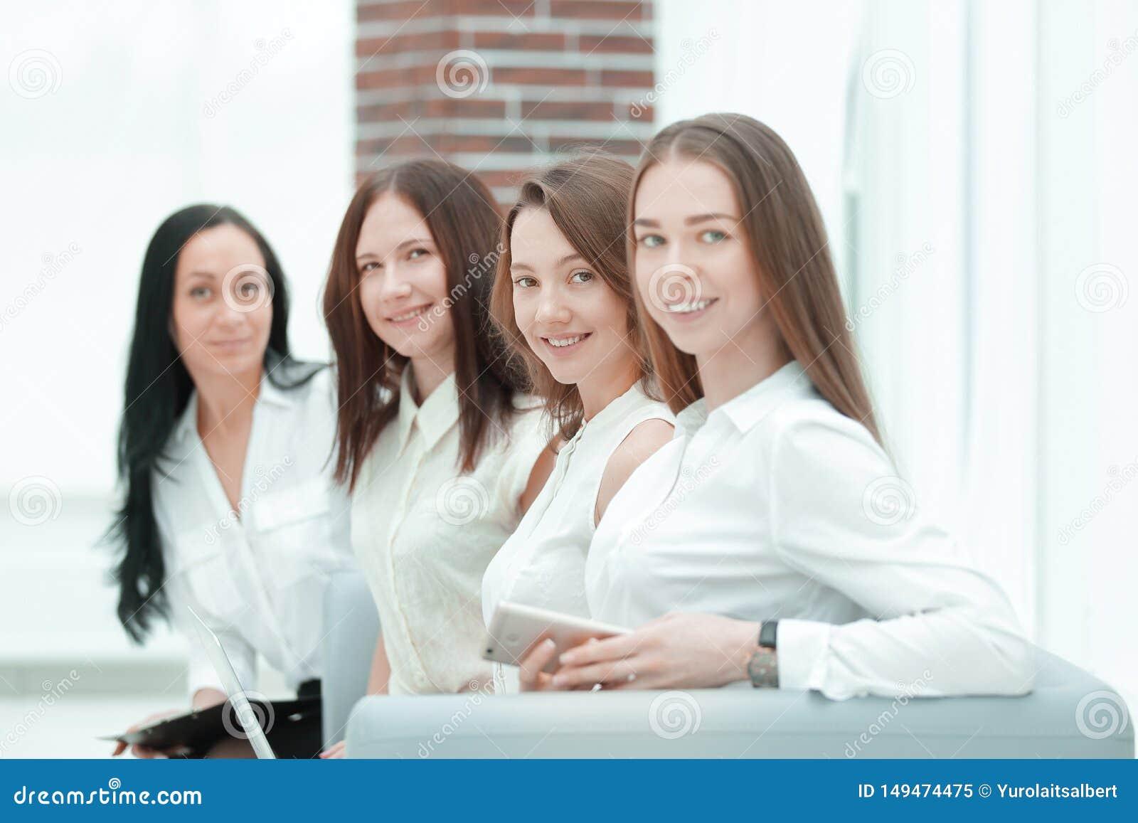 Grupo de mujer de negocios acertada que se sienta en pasillo de la oficina Foto con el espacio de la copia