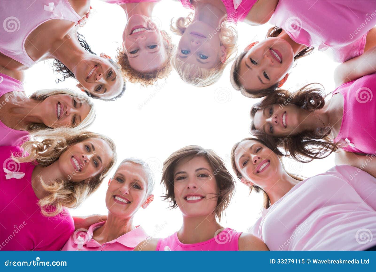 Grupo de mujeres felices en el rosa que lleva del círculo para el cáncer de pecho