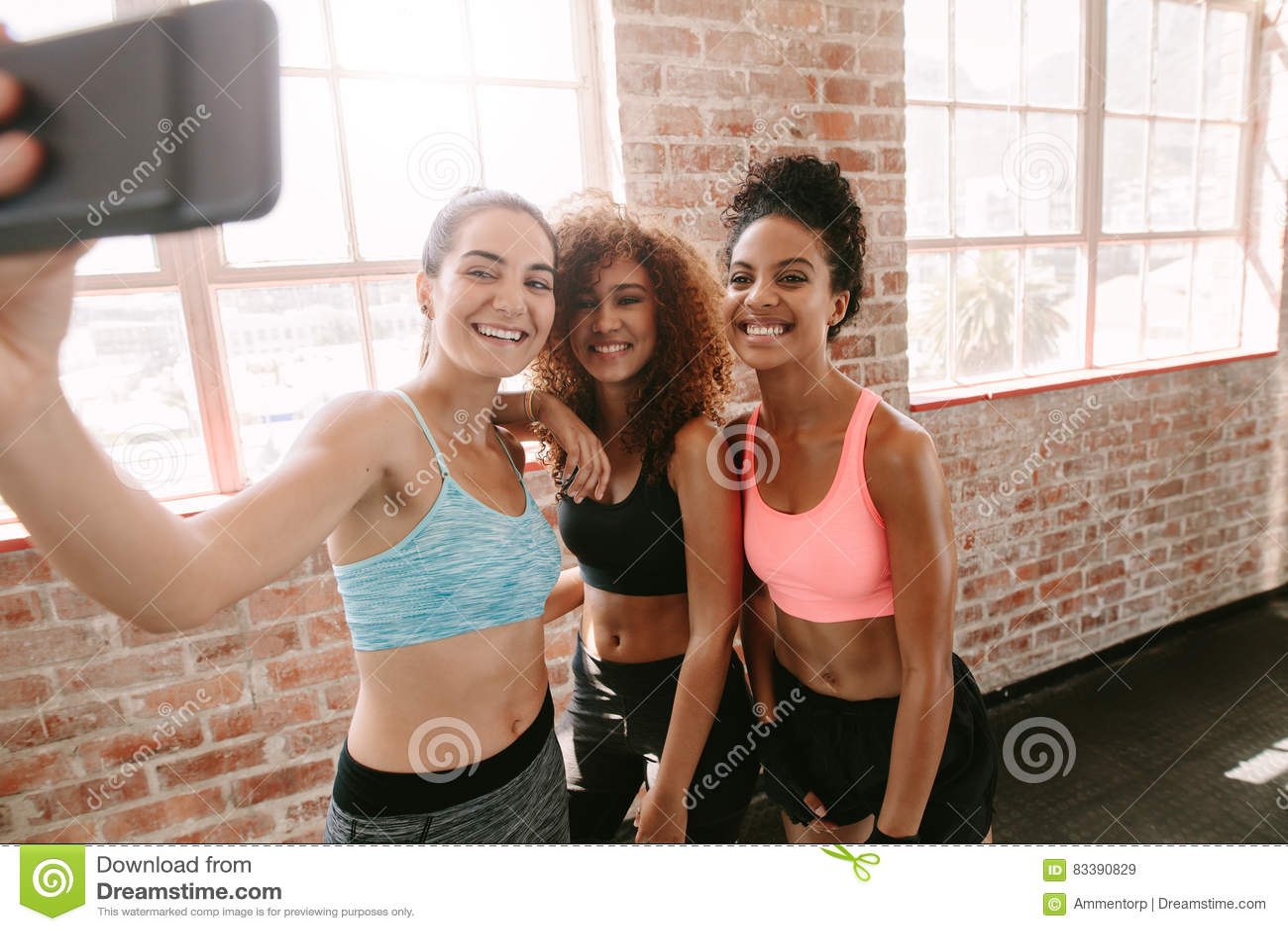 Grupo de mujeres jovenes felices que toman el selfie en gimnasio