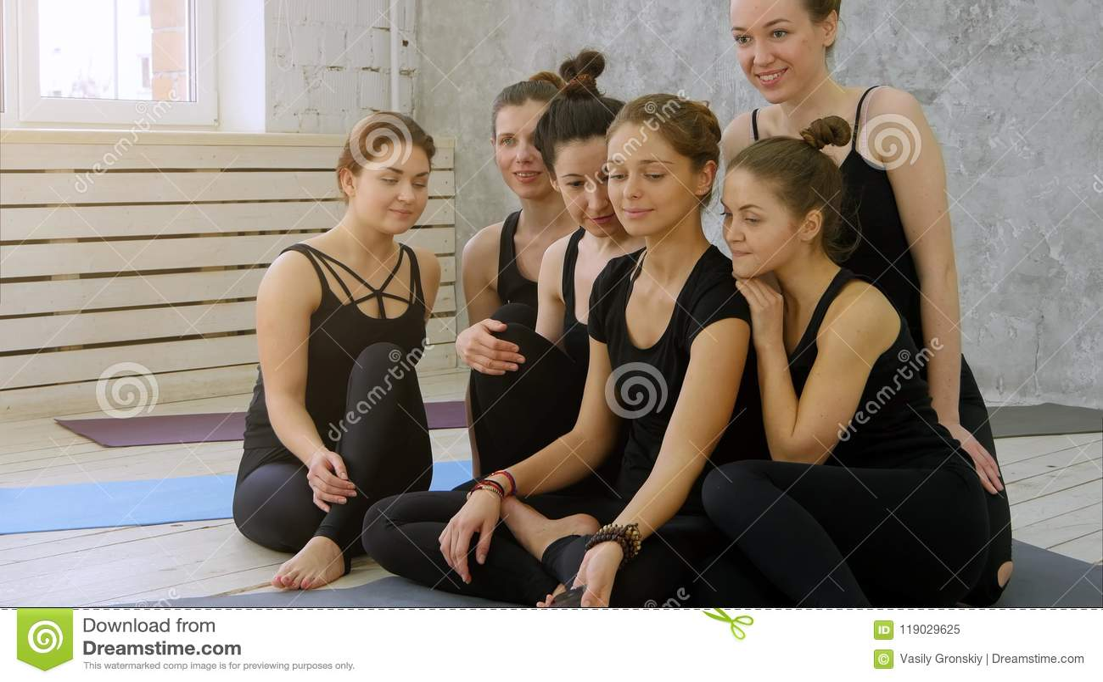 Grupo de mujeres jovenes que toman el selfie usando el teléfono celular en la clase de la yoga