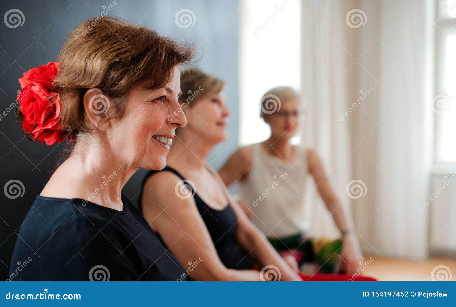 Grupo de mujeres mayores que asisten a la clase de baile, descansando