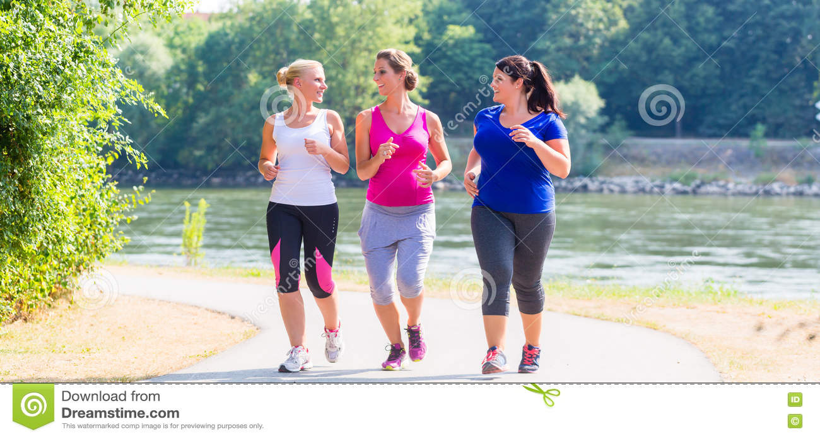 Grupo de mujeres que corren en activar de la orilla del lago