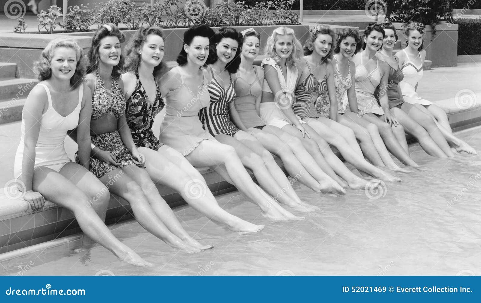 Grupo de mujeres que se sientan en fila en el lado de la piscina (todas las personas representadas no son vivas más largo y ningú